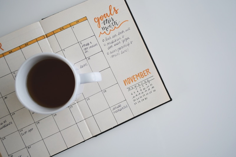 photo showing a  planner and a cup of coffee